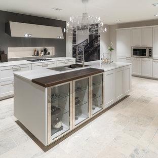 Offene, Zweizeilige, Große Klassische Küche mit integriertem Waschbecken, weißen Schränken, Küchenrückwand in Grau, Küchengeräten aus Edelstahl, Kücheninsel, beigem Boden, weißer Arbeitsplatte und Schrankfronten im Shaker-Stil in Köln