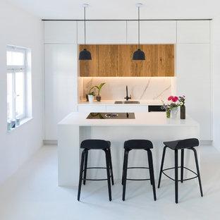 Offene, Einzeilige, Mittelgroße Moderne Küche mit Unterbauwaschbecken, hellen Holzschränken, Laminat-Arbeitsplatte, schwarzen Elektrogeräten, Kücheninsel, weißem Boden, weißer Arbeitsplatte, flächenbündigen Schrankfronten und Küchenrückwand in Weiß in Stuttgart