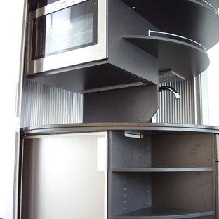 Bild på ett funkis svart svart kök och matrum, med en nedsänkt diskho, granitbänkskiva, svart stänkskydd, rostfria vitvaror, heltäckningsmatta och svart golv