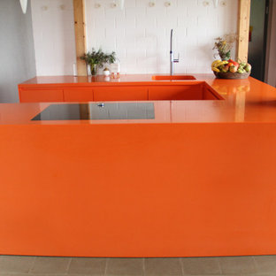 Immagine di una cucina design di medie dimensioni con lavello sottopiano, ante lisce, ante arancioni, top in superficie solida, elettrodomestici neri, pavimento grigio e top arancione