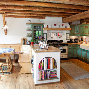 Landhaus Wohnküche in U-Form mit Landhausspüle, grünen Schränken, Arbeitsplatte aus Holz, Küchenrückwand in Weiß, weißen Elektrogeräten, braunem Holzboden, Halbinsel, freigelegten Dachbalken und Schrankfronten mit vertiefter Füllung in München