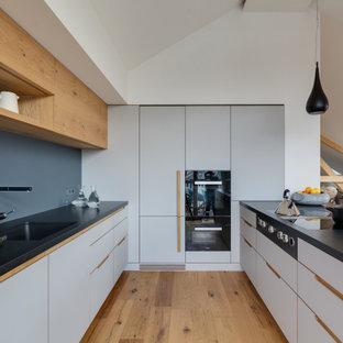 Mittelgroße Moderne Küche in U-Form mit Unterbauwaschbecken, flächenbündigen Schrankfronten, weißen Schränken, schwarzen Elektrogeräten, braunem Holzboden, Halbinsel, braunem Boden, schwarzer Arbeitsplatte und gewölbter Decke in München
