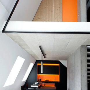 Modelo de cocina minimalista, abierta, con armarios con paneles lisos, puertas de armario negras, salpicadero naranja, una isla, suelo gris y encimeras negras