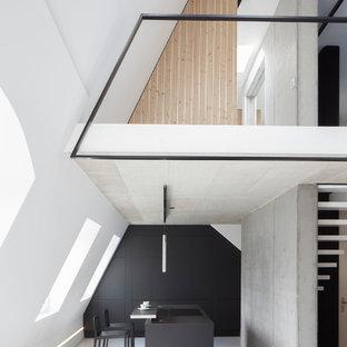На фото: кухня-гостиная в стиле модернизм с плоскими фасадами, черными фасадами, оранжевым фартуком, островом, серым полом и черной столешницей с