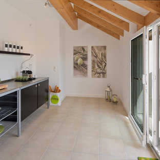 Mid-sized contemporary enclosed kitchen pictures - Enclosed kitchen - mid-sized contemporary single-wall limestone floor enclosed kitchen idea in Frankfurt with open cabinets, no island, black cabinets, stainless steel countertops and white backsplash