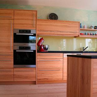 ニュルンベルクの中サイズのコンテンポラリースタイルのおしゃれなキッチン (アンダーカウンターシンク、インセット扉のキャビネット、木材カウンター、黄色いキッチンパネル、ガラス板のキッチンパネル、淡色無垢フローリング、ベージュの床、ベージュのキッチンカウンター) の写真