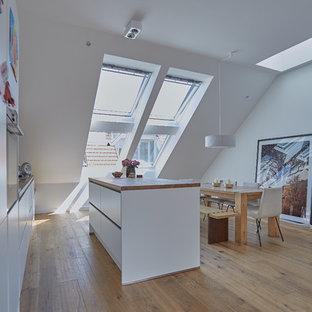Offene, Zweizeilige, Mittelgroße Moderne Küche mit flächenbündigen Schrankfronten, weißen Schränken, Arbeitsplatte aus Holz, braunem Holzboden, Kücheninsel, braunem Boden und brauner Arbeitsplatte in Berlin