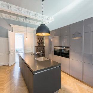 Geschlossene Moderne Küche mit Waschbecken, flächenbündigen Schrankfronten, grauen Schränken, schwarzen Elektrogeräten, hellem Holzboden, Kücheninsel, beigem Boden und schwarzer Arbeitsplatte in Frankfurt am Main