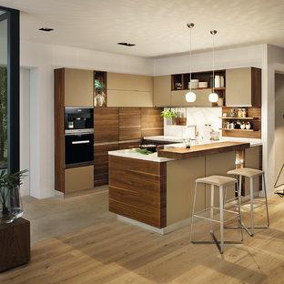 Offene, Große Moderne Küche in U-Form mit flächenbündigen Schrankfronten, hellbraunen Holzschränken, Halbinsel, hellem Holzboden und beigem Boden in Hannover