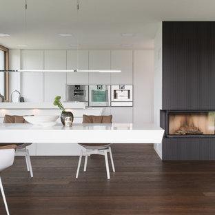 Offene, Zweizeilige, Große Moderne Küche mit flächenbündigen Schrankfronten, weißen Schränken, Küchengeräten aus Edelstahl, dunklem Holzboden, braunem Boden, Halbinsel und weißer Arbeitsplatte in Stuttgart