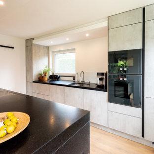 Zweizeilige, Mittelgroße Moderne Küche mit flächenbündigen Schrankfronten, grauen Schränken, Granit-Arbeitsplatte, schwarzen Elektrogeräten, Kücheninsel, schwarzer Arbeitsplatte, Unterbauwaschbecken, Küchenrückwand in Weiß, hellem Holzboden und beigem Boden in München