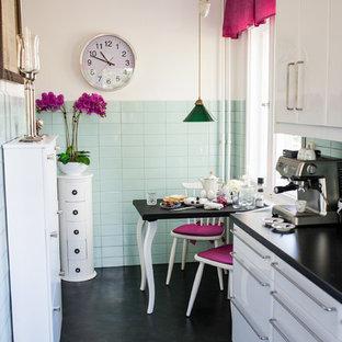 Geschlossene, Zweizeilige, Mittelgroße Retro Küche ohne Insel mit weißen Schränken, schwarzem Boden, schwarzer Arbeitsplatte, flächenbündigen Schrankfronten, Küchenrückwand in Grün, Rückwand aus Keramikfliesen und Linoleum in Berlin