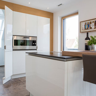 This is an example of a mid-sized contemporary l-shaped open plan kitchen in Frankfurt with a drop-in sink, flat-panel cabinets, white cabinets, granite benchtops, black splashback, glass sheet splashback, stainless steel appliances, terra-cotta floors, a peninsula, brown floor and black benchtop.
