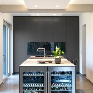 Offene, Zweizeilige, Große Moderne Küche mit integriertem Waschbecken, flächenbündigen Schrankfronten, grauen Schränken, Edelstahl-Arbeitsplatte, schwarzen Elektrogeräten, Zementfliesen, Kücheninsel, beigem Boden und weißer Arbeitsplatte in Sonstige