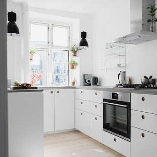 Small scandinavian u-shaped open plan kitchen in Berlin with flat-panel cabinets, white cabinets, concrete benchtops, white splashback, light hardwood floors, no island and stainless steel appliances.