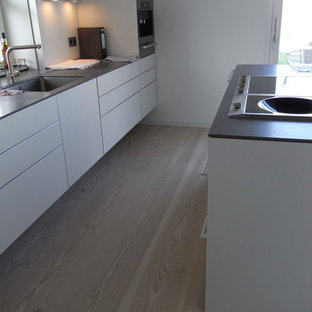 Inspiration for a mid-sized scandinavian galley open plan kitchen in Berlin with an integrated sink, flat-panel cabinets, light wood cabinets, limestone benchtops, white splashback, ceramic splashback, stainless steel appliances, light hardwood floors and with island.