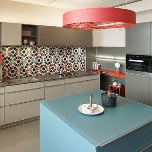 Moderne Küche mit Waschbecken, flächenbündigen Schrankfronten, grauen Schränken, bunter Rückwand, schwarzen Elektrogeräten, Kücheninsel, grauem Boden und grauer Arbeitsplatte in Frankfurt am Main
