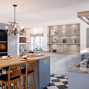 This is an example of a mid-sized traditional u-shaped separate kitchen in Berlin with an undermount sink, beaded inset cabinets, blue cabinets, granite benchtops, grey splashback, stone slab splashback, panelled appliances, ceramic floors and with island.