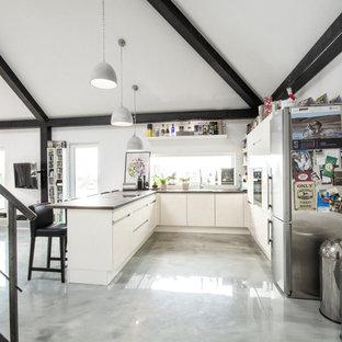 Offene, Große Moderne Küche in U-Form mit flächenbündigen Schrankfronten, weißen Schränken, Küchengeräten aus Edelstahl, Halbinsel, grauem Boden und brauner Arbeitsplatte in Berlin