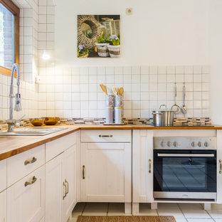 Klassische Küche in L-Form mit Einbauwaschbecken, Schrankfronten im Shaker-Stil, weißen Schränken, Arbeitsplatte aus Holz, Küchenrückwand in Weiß, Küchengeräten aus Edelstahl, weißem Boden und brauner Arbeitsplatte in Sonstige