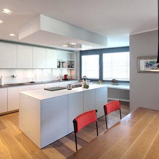 Offene, Einzeilige, Geräumige Moderne Küche mit Waschbecken, flächenbündigen Schrankfronten, weißen Schränken, Küchenrückwand in Weiß, Glasrückwand, Kücheninsel, braunem Holzboden und braunem Boden in Bonn