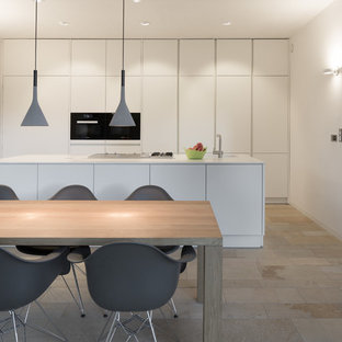 Large contemporary eat-in kitchen in Other with flat-panel cabinets, white cabinets, white splashback, black appliances, with island, travertine floors and an integrated sink.