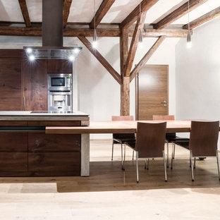 Esempio di una grande cucina abitabile minimal con ante lisce, ante in legno bruno, elettrodomestici in acciaio inossidabile, parquet chiaro, penisola e top in cemento
