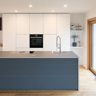 Mid-sized modern open concept kitchen pictures - Inspiration for a mid-sized modern single-wall medium tone wood floor and brown floor open concept kitchen remodel in Stuttgart with flat-panel cabinets, white cabinets, laminate countertops, an island, blue countertops and a drop-in sink