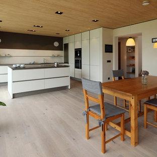 Offene, Große Moderne Küche in L-Form mit Einbauwaschbecken, flächenbündigen Schrankfronten, weißen Schränken, Küchenrückwand in Schwarz, schwarzen Elektrogeräten, hellem Holzboden, Kücheninsel und beigem Boden in München