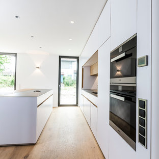 Inspiration for an expansive contemporary galley open plan kitchen in Munich with an integrated sink, flat-panel cabinets, white cabinets, stainless steel benchtops, medium hardwood floors and with island.