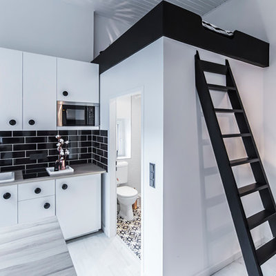 Small trendy single-wall light wood floor eat-in kitchen photo in Dusseldorf with a farmhouse sink, flat-panel cabinets, white cabinets, black backsplash, subway tile backsplash, stainless steel appliances, wood countertops and a peninsula