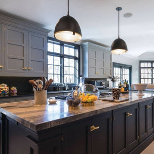 This is an example of a large country l-shaped eat-in kitchen in Munich with an integrated sink, beaded inset cabinets, grey cabinets, granite benchtops, black splashback, glass sheet splashback, stainless steel appliances, travertine floors, with island, beige floor and brown benchtop.
