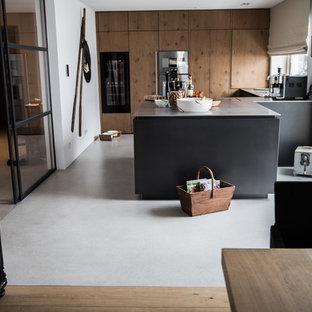 Mittelgroße Moderne Wohnküche in U-Form mit flächenbündigen Schrankfronten, schwarzen Elektrogeräten, Betonboden, Halbinsel, grauem Boden und grauer Arbeitsplatte in München