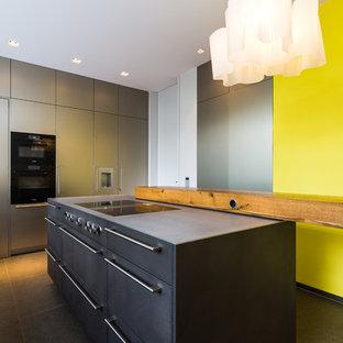 フランクフルトの大きいコンテンポラリースタイルのおしゃれなキッチン (一体型シンク、フラットパネル扉のキャビネット、ヴィンテージ仕上げキャビネット、ステンレスカウンター、黄色いキッチンパネル、シルバーの調理設備の、グレーの床、グレーのキッチンカウンター) の写真
