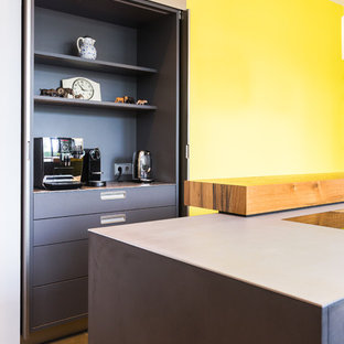 Small modern galley kitchen pantry in Frankfurt with flat-panel cabinets, stainless steel cabinets, stainless steel worktops, yellow splashback and grey worktops.