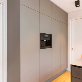 Photo of a mid-sized contemporary galley open plan kitchen in Frankfurt with an integrated sink, flat-panel cabinets, brown cabinets, stainless steel benchtops, black appliances, light hardwood floors, no island, brown floor and grey benchtop.