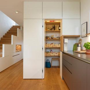 ミュンヘンの大きいコンテンポラリースタイルのおしゃれなキッチン (一体型シンク、フラットパネル扉のキャビネット、白いキャビネット、コンクリートカウンター、白いキッチンパネル、木材のキッチンパネル、シルバーの調理設備の、無垢フローリング、茶色い床、グレーのキッチンカウンター) の写真