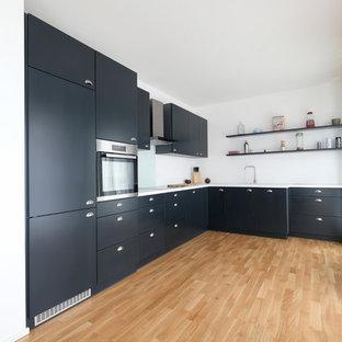 Offene, Mittelgroße Moderne Küche ohne Insel in L-Form mit Einbauwaschbecken, flächenbündigen Schrankfronten, blauen Schränken, Küchenrückwand in Blau, Glasrückwand, Küchengeräten aus Edelstahl, braunem Holzboden und braunem Boden in Köln