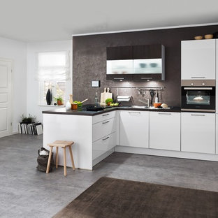 Mid-sized contemporary l-shaped open plan kitchen in Hanover with flat-panel cabinets, white cabinets, brown splashback, black appliances, concrete floors, a peninsula, grey floor, brown benchtop, granite benchtops and slate splashback.