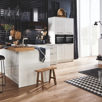 Example of a small trendy single-wall medium tone wood floor and brown floor eat-in kitchen design in Hanover with shaker cabinets, white cabinets, black backsplash, subway tile backsplash, black appliances, a peninsula, white countertops and glass countertops