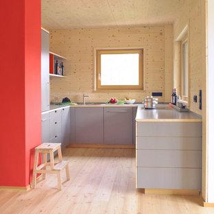 Ejemplo de cocina en U, escandinava, pequeña, abierta, sin isla, con fregadero encastrado, armarios con paneles lisos, puertas de armario grises, salpicadero marrón y suelo de madera clara