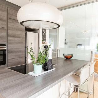 Geschlossene, Zweizeilige, Kleine Moderne Küche mit flächenbündigen Schrankfronten, hellbraunen Holzschränken, Arbeitsplatte aus Holz, schwarzen Elektrogeräten, hellem Holzboden, Kücheninsel, beigem Boden und brauner Arbeitsplatte in Hannover