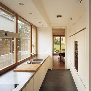 ベルリンの中くらいのコンテンポラリースタイルのおしゃれなキッチン (ダブルシンク、フラットパネル扉のキャビネット、ベージュのキャビネット、ステンレスカウンター、ガラス板のキッチンパネル、アイランドなし) の写真