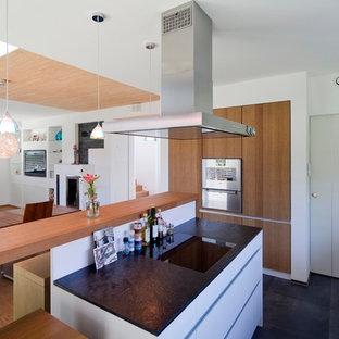 Offene, Mittelgroße Moderne Küche in U-Form mit flächenbündigen Schrankfronten, Küchengeräten aus Edelstahl, Schieferboden, Halbinsel, schwarzem Boden und schwarzer Arbeitsplatte in München