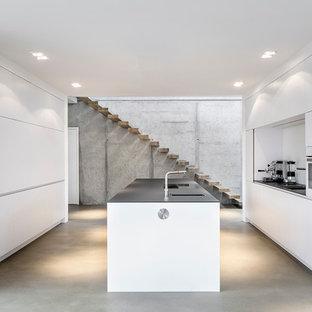 Offene, Einzeilige, Mittelgroße Moderne Küche mit flächenbündigen Schrankfronten, weißen Schränken, Küchenrückwand in Weiß, Kücheninsel, Waschbecken und Betonboden in Düsseldorf