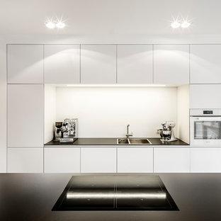 ケルンのモダンスタイルのおしゃれなキッチン (ダブルシンク、フラットパネル扉のキャビネット、白いキャビネット、白いキッチンパネル、白い調理設備、コンクリートの床) の写真