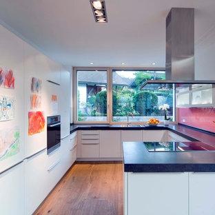 Offene Moderne Küche in U-Form mit Einbauwaschbecken, flächenbündigen Schrankfronten, weißen Schränken, Küchenrückwand in Rosa, Glasrückwand, schwarzen Elektrogeräten, braunem Holzboden, Halbinsel, braunem Boden und blauer Arbeitsplatte in München