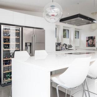 Mittelgroße Moderne Küche in L-Form mit Einbauwaschbecken, flächenbündigen Schrankfronten, weißen Schränken, Küchengeräten aus Edelstahl, Kücheninsel, grauem Boden und weißer Arbeitsplatte in Dortmund