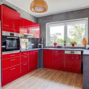 Offene, Mittelgroße Moderne Küche ohne Insel in U-Form mit Einbauwaschbecken, flächenbündigen Schrankfronten, roten Schränken, Glasrückwand, Küchengeräten aus Edelstahl, Vinylboden, braunem Boden und grauer Arbeitsplatte in Berlin