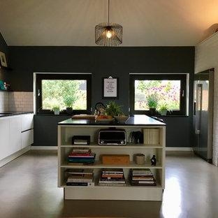 ハノーファーの中サイズのコンテンポラリースタイルのおしゃれなキッチン (ドロップインシンク、フラットパネル扉のキャビネット、クオーツストーンカウンター、グレーの床、白いキャビネット、黒い調理設備、クッションフロア、黒いキッチンカウンター) の写真